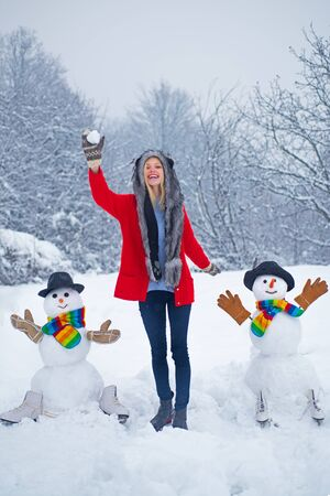 Happy girl plaing with a snowman on a snowy winter walk. Happy girl snowman and winter fun. Merry Christmas and happy new year greeting card with copy-space.