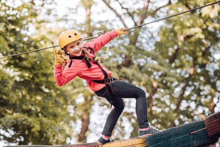 High ropes walk. Active children. Playground. Eco Resort Activities. Happy child boy calling while climbing high tree and ropes. Safe Climbing extreme sport with helmet.