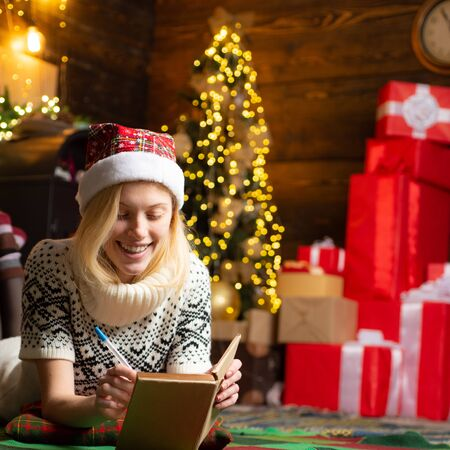 The end of the working year. Waiting for Christmas. List of goals in the new year. Tracker mood. The girl smiling and making notes in her diary. Imagens