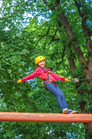 Climber child on training. Child climbing on high rope park. Cargo net climbing and hanging log. Children fun. Portrait of a beautiful kid on a rope park among trees. Cute baby playing.