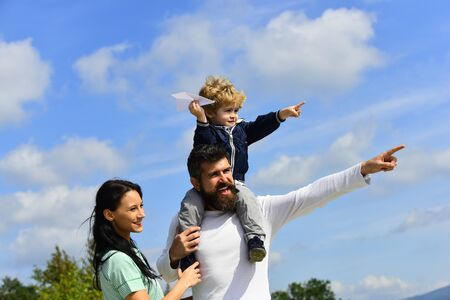 Happy family father and child on meadow with a kite in the summer on the nature. Enjoy. Happy family - child son playing with paper airplane. Generation. Parenting. Stock Photo