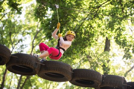 Eco Resort Activities. Climber little girl on training. Children fun. Rope park. Active children. Playground. Climber child. Teenager girl adventure and travel. Adventure climbing high wire park.