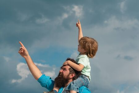 Fathers day. Cute boy with dad playing outdoor. Happy child pointing on summer sky background. Foto de archivo - 124925248