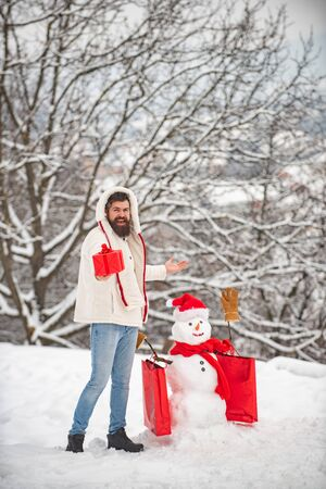 Funny snowman with shopping bag - discount and winter sale concept. Happy smiling snow man on sunny winter day with Happy father. Copy space.