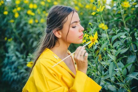 The girl paints a yellow flower. The process of reproduction of the plant. Health and longevity with medicinal plants.
