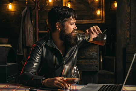 The biker coming to the bar. Frustrated man with a beard is drinking from a bottle of whiskey. Problems in relationships. Alcoholism, alcohol addiction and people concept.