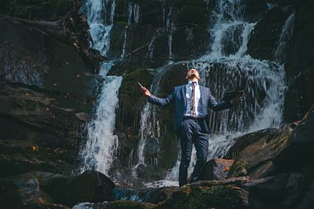 Young handsome man in wet office suit holding Laptop under the water on nature background. Fantasy about the rest. Burnout in the workplace concept. Stok Fotoğraf
