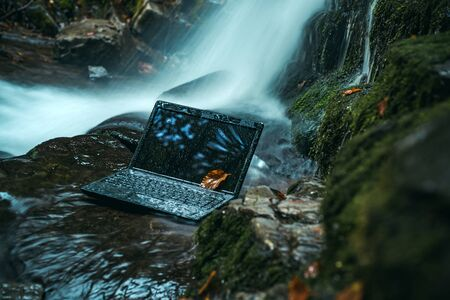 Laptop under the surface of the water on nature background. Testing technology for stability. Stockfoto