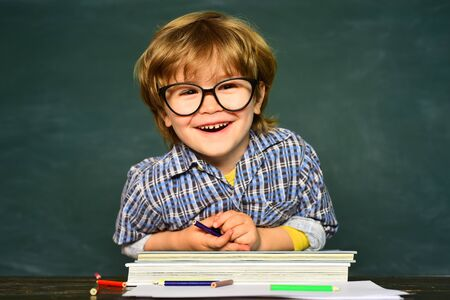 Back to school and happy time. Funny little boy in glasses on blackboard background. Kid with a book.