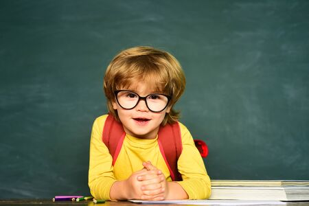 Happy mood smiling broadly in school. Funny little boy pointing up on blackboard. Back to school. School and education concept. Stock Photo