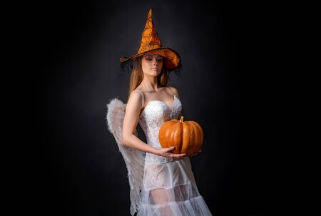 Celebrating happy Thanksgiving day. Fashion Glamour Halloween art design. Happy Halloween Angelic Witch. Cute girl in angel costume on black wall background.