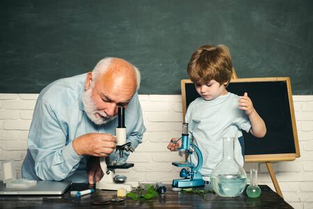 Microbiology science. Little kids scientist earning Biology in school lab. School concept. Chalkboard copy space. Imagens