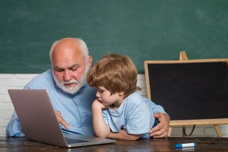 Teacher and child. His enjoys talking to grandfather. Daddy and son together. Young serious male Pupil studying in school. Back to school. Old teacher.