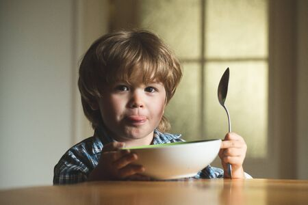 Baby eating food on kitchen. Cute kid are eating. Laughing cute child baby boy sitting in highchair and eating on blurred background.