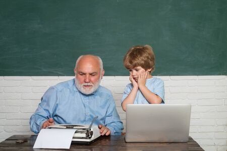 Pupil preparing for test or exam. Man teaches child. Young serious male Pupil studying in school. Portrait of confident old male teacher. Learning and education concept. Imagens - 124925284