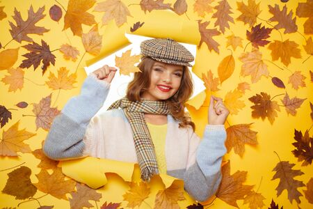 This blanket scarf has a lovely soft feel. Fashion girl look through torn paper with autumn leaves. Cute woman wear autumn fashion accessories. Fall look of vogue model. Casual fashion trend for fall Stock Photo