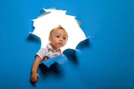 Un futuro brillante. El niño pequeño mira a través del papel rasgado. Niño cortando la pared azul. Niño curioso mira fuera del agujero en el papel. Entrada a una nueva vida o comienzo. Ser curioso