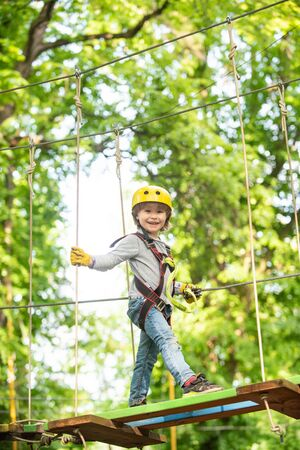 Toddler kindergarten. Active children. Balance beam and rope bridges. Toddler age. Cute child boy. Rope park - climbing center. Helmet and safety equipment.