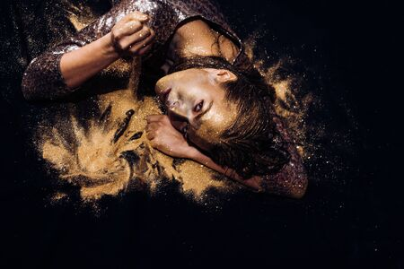 Vogue and glamour concept. Golden skin. Attractive woman pretty face with makeup and body art metallized color. Spa and wellness. Golden mask. Luxury beauty procedure. Pure gold. Golden lady relaxing
