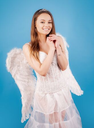 Cupid cute angel - Concept of Valentines Day. Valentine Day Gift Card - Holiday teen Cupid with Love. Cute little female cupid. Halloween people in angel costume. Stock Photo