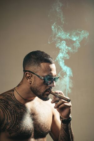 Expensive tobacco. Tattooed man with cigar. Cigar smoking enjoy life moment. Bearded muscular macho beautiful torso fashion sunglasses smoking cigar. Elite tobacco. Pure enjoyment. Consuming tobacco