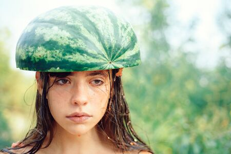 Cheerful beautiful girl wearing a watermelon on her head. Sunny day. The biggest discounts for all autumn clothes for girls. Crazy people.