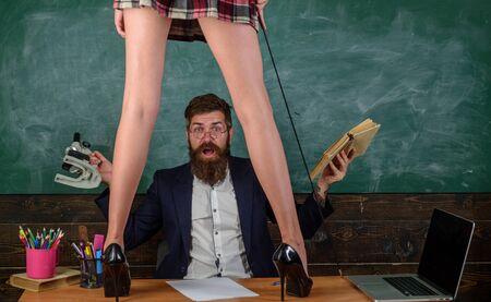 Mężczyzna brodaty nauczyciel i kobiece nogi mini spódniczka. Nauka kobiecego ciała. Dominacja i uległość. Pożądany uczeń z batem na wysokich obcasach stoją na stole. Edukacja seksualna. Seks rola gra Zdjęcie Seryjne