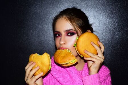 Fashion, beauty.Sexy woman with perfect makeup eating hamburgers. Female beauty visage concept.