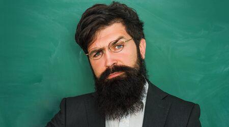 Portrait of bearded professor at school lesson at desks in classroom - close up. Professor in class on blackboard background. Tutoring. Imagens
