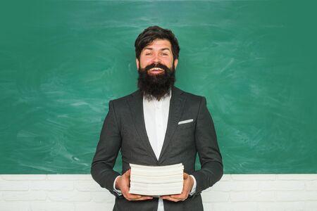 Professor in class on blackboard background. Tutoring. Young bearded teacher near chalkboard in school classroom. Teachers day - knowledge and educational school concept.