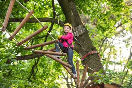 Climber child on training. Happy child boy calling while climbing high tree and ropes. Climber child on training. Artworks depict games at eco resort which includes flying fox or spider net. Stock Photo