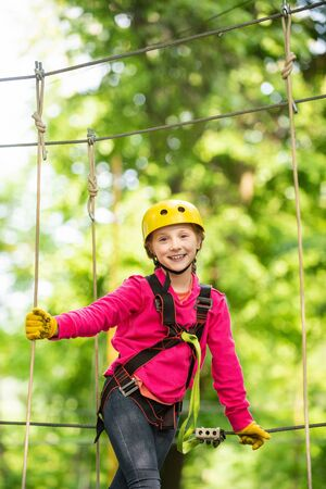 Little girl climbing in adventure activity park with helmet and safety equipment. Enjoy childhood years. Helmet and safety equipment.