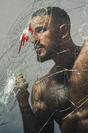 Handsome brutal man near broken glass. Brutal handsome macho focused on fight result. Want to fight right now. Fight concept. Man muscular body punching. Concentrated on target. Destroy obstacles