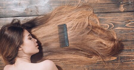 Woman with beautiful long hair on wooden background. Long hair. Beautiful hair coloring woman. Fashion haircut. 免版税图像