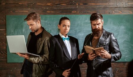 People with laptop book stand in school classroom. School teachers. Bearded man masculine girl and handsome guy school colleagues. Teaching and education occupation. Diversity concept. School staff