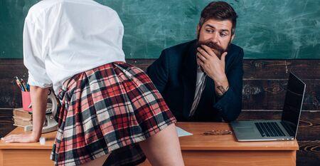 Profesor de hombre barbudo y piernas de minifalda femenina. Concepto de lección erótica. Subordinado y sumisión. Estudiante deseable. Educación sexual para todas las edades. Aprendiz curioso. Juego de rol sexual