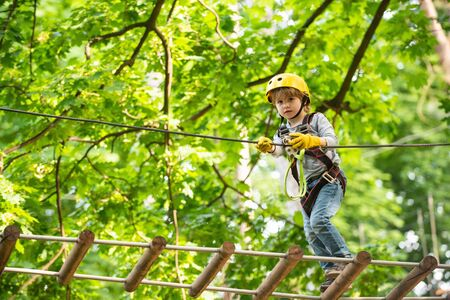 Beautiful little child climbing and having fun in adventure Park. Toddler kindergarten. Children summer activities. Child climbing on high rope park. Small boy enjoy childhood years