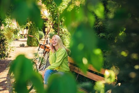I am in park already waiting for you. Blonde enjoy relax in park or garden. Active girl with bicycle. Woman with bicycle in blooming park garden. Active leisure and lifestyle. Girl calling friend