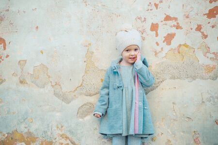 autumn fashion. childrens day. little girl in vintage coat on grunge background. Beauty. retro style. copy space. small kid spring clothes. happy childhood. fashion child in autumn coat
