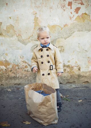 shopping. childrens day. small kid with shopping bag. happy childhood. holiday shopping. ready for date. little boy in vintage coat. Beauty. retro style. vintage trendy look. stylish child after shop Stock Photo