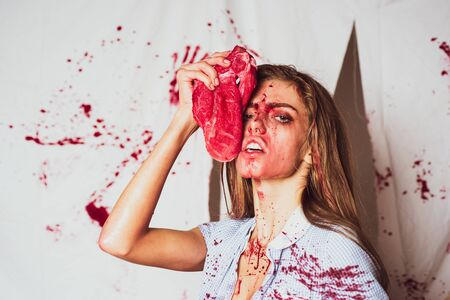 Dependence on acute sensations. Steak or beefsteak - bloody meat. Sexy woman covered in blood holding knife. Revenge of the lover. Toxics relationship concept.