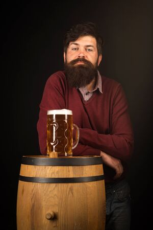 Bearded man with a glass of beer. Concept of craft beer. Man with beer on balck background.