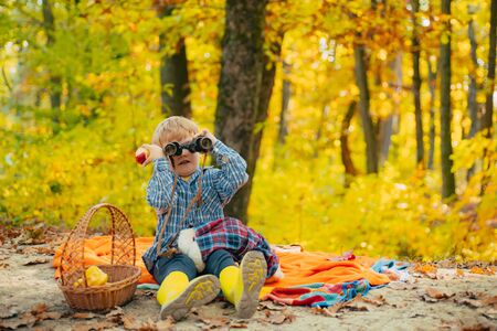 Boy in rubber boots relaxing in forest sit picnic blanket. Cute tourist concept. He likes hiking. Kid with toy sit on plaid forest picnic. Child relax in autumn nature. Autumn picnic with teddy bear Imagens