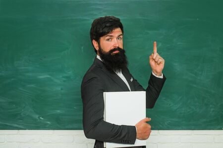 Exam in college. Preparing for exam in college. Teacher job - profession and learning concept. Education. Chalkboard copy space. Friendly teacher in classroom near blackboard desk. Stock Photo