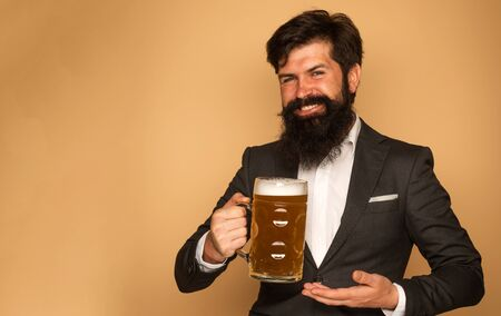 Hipster in black suit relaxing at pub. Emotional funny bearded drunk hipster holds craft bottled beer. Handsome barman holding a pint of beer. Stock Photo