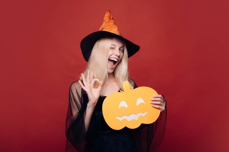 Attractive model girl in Halloween costume. Happy young woman in witch halloween costume on party over isolated background. Surprised woman in witches hat and short dress. Helloween people concept.