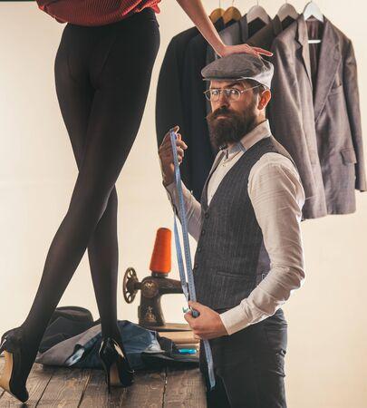 Er ist ein Meisterschneider. Bärtiger Mann, der weibliche Kleidung in Schneiderei schneidert. Professioneller Schneider oder Modedesigner bei der Arbeit. Damenschneiderei Modekleidung