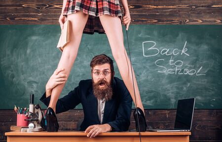 Domination and submission. Desirable sexy student with whip high heels stand on table. Sex education. Sex role game. Man bearded teacher and female mini skirt sexy legs. Learning sexy female body 免版税图像