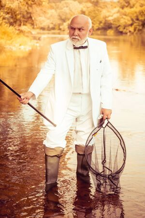 Senior man fishing and relaxing while enjoying hobby. Difference between fly fishing and regular fishing. Old mature Man fisherman catches a fish. Retro, vintage. Stock Photo