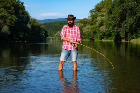 Man fisherman catches a fish. Fly fishing. Brown trout being caught in fishing net. American angler fishing. Brown trout fish. Fisherman. Stock Photo